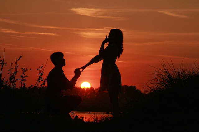 man proposing to woman with sunset